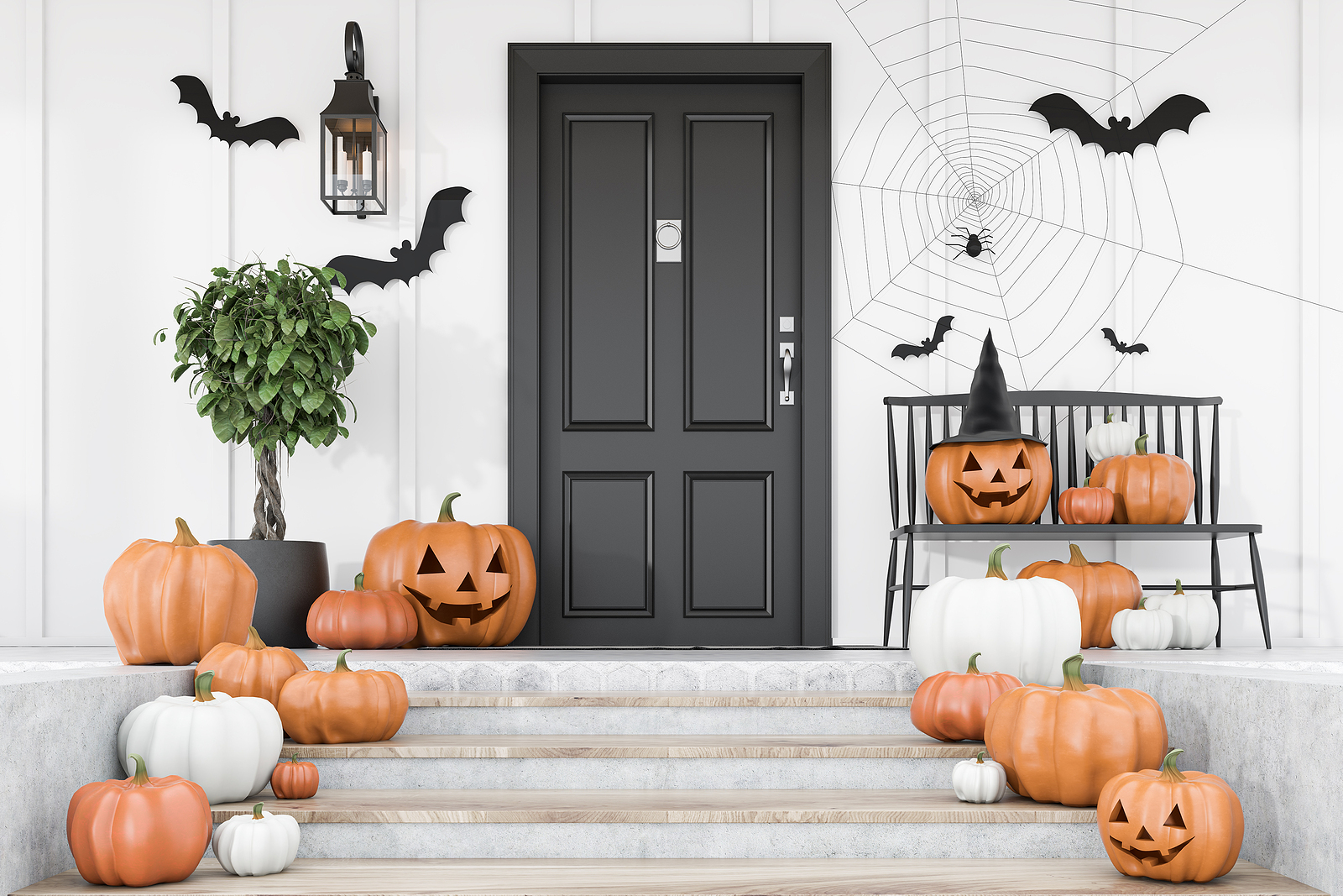 Front porch decorated with pumpkins, bats, and spiders for Halloween