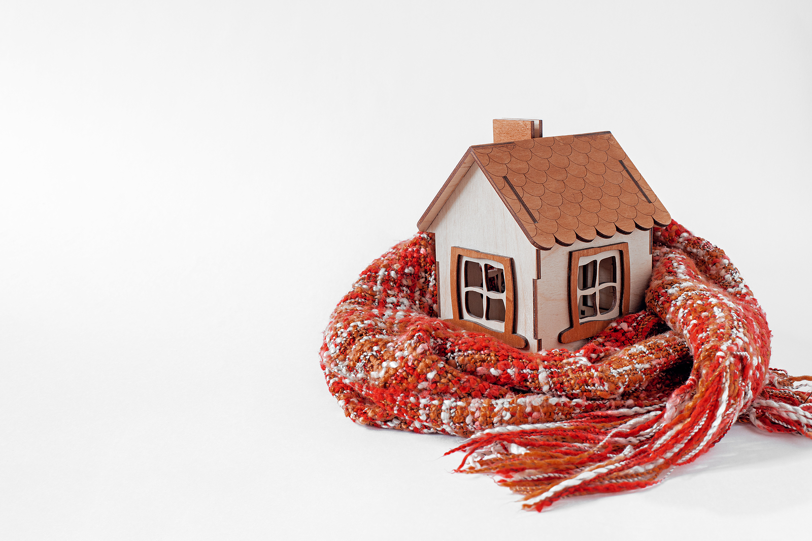 Small, toy house wrapped in a scarf.